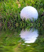 Difficult Shot! A golf ball on a tee in the rough and very close to a water hazard — Stock Photo