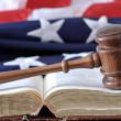 Stock Photo: Gavel over weathered book with flag in background.