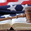 Stockfoto: Gavel over weathered book with flag in background.