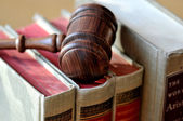 A wooden gavel atop books — Stock Photo