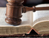 Gavel over weathered book in a portrayal of judicial system — Stok fotoğraf