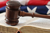 Gavel over weathered book with flag in background — Foto de Stock
