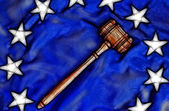 Wooden gavel atop flag — Stock Photo