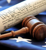 Closeup of gavel with constitution and flag in background — Stock Photo