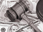 Wooden gavel atop US currency. — Stock Photo