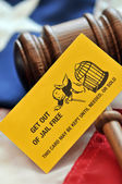 Yellow playing card with gavel atop US flag — Stock Photo