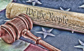 US constitution with wooden judge's gavel over American flag background — Stock Photo