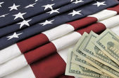 US currency and American flag — Stock Photo