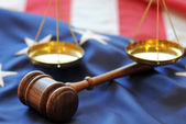 Gavel and scales atop flag background — Stock Photo