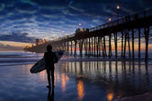 Surfer admire sunset near Oceanside Pier — Stock Photo