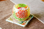 Colorful bright glass candlestick on the beige textile cover — Photo