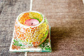 Colorful bright glass candlestick on the beige textile cover — Stok fotoğraf