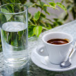 White espresso cup with glass of cold water — Stock Photo #30677605