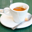White espresso cup, biscuit and glass of cold water — Stock Photo