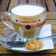 Glass capuccino cup with biscuit — Stock Photo