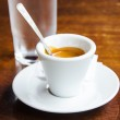 White espresso cup with glass of cold water — Stock Photo