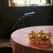 Golden crown on red desk in dark room — Stock Photo