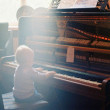 Child playing on old broken piano — Stock Photo #34382105