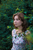 Young beautiful girl standing in the bushes at dusk — Stock Photo