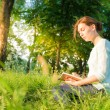 Young beautiful girl sitting in a park and writing in a notebook — Стоковое фото #49814057