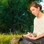 chica joven y bella sentados en un parque y escribiendo en un cuaderno — Foto de Stock   #49814047
