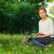Young beautiful girl sitting in a park and writing in a notebook — Стоковое фото #49814049