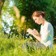 Young beautiful girl sitting in a park and writing in a notebook — Стоковое фото #49814055