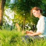 chica joven y bella sentados en un parque y escribiendo en un cuaderno — Foto de Stock   #49814057