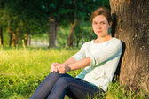 Young beautiful girl with big blue eyes sitting in the park in t — Stock Photo