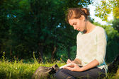 Young beautiful girl sitting in a park and writing in a notebook — Stock fotografie