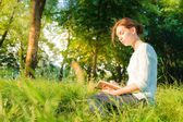 Young beautiful girl sitting in a park and writing in a notebook — Stock Photo