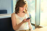 Girl in cafe with headphones and cell phone — Stock Photo