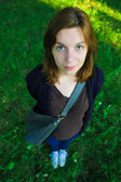 Young beautiful girl with big blue eyes standing in the park and — Stock fotografie