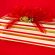 Red, Gold and White Striped Gift Package with Red Ribbons — Stockfoto