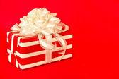 Rote und weiße gestreifte Geschenk mit weißen Bändern — Stockfoto