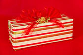 Red, Gold and White Striped Gift Package with Red Ribbons — Stock Photo