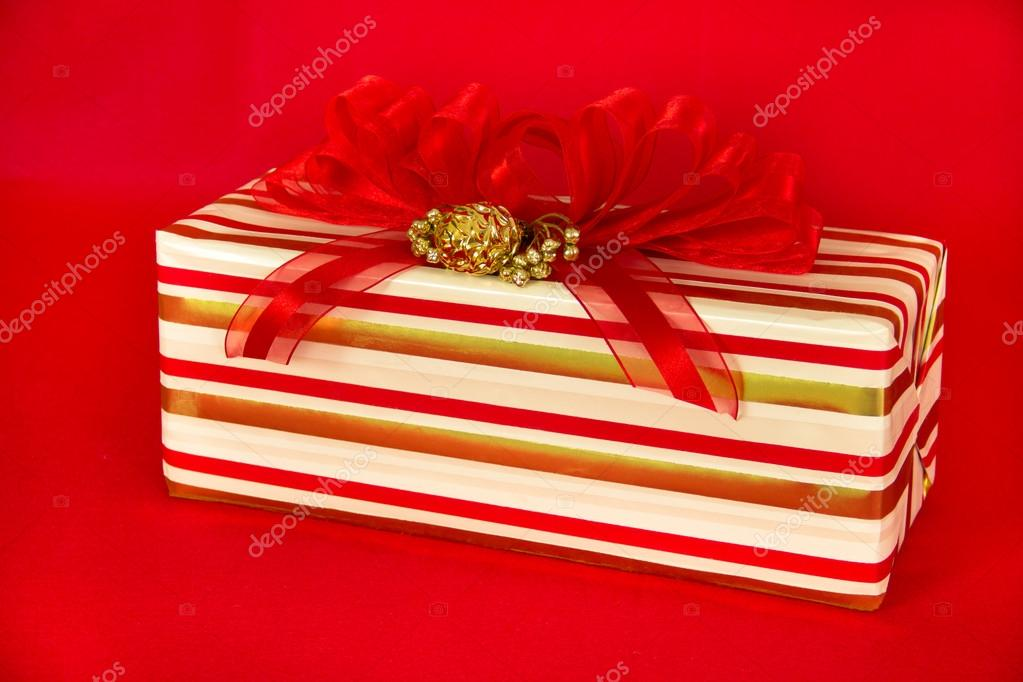 A gift wrapped in red, gold and white striped paper is topped by a red striped bow and gold decorations.  Stock Photo #12271998
