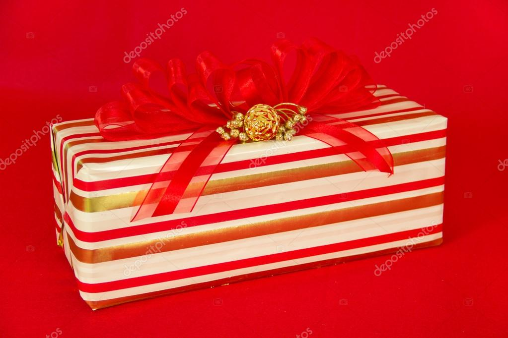 A gift wrapped in red, gold and white striped paper is topped by a red striped bow and gold decorations.  Stock Photo #12272014