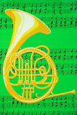 French Horn on Green Music Sheet — Stock Photo