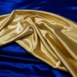 Royalty-Free Stock Photo: Gold Satin Drape on Blue Satin
