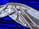 Silver Satin Drape on Blue Satin — Stock Photo