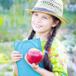 Girl with book and red apple in summer day - Stock Photo