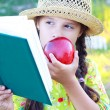 Stock Photo: Girl with book and red apple in summer day
