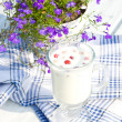 Milk with raspberries in cup and flowers - Stock Photo