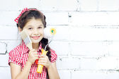 Girl stays with paint brush and roller in hand — Stock Photo