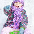Girl rolls down hill in winter park - Stock Photo