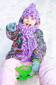 Girl rolls down hill in winter park — Stock Photo