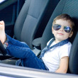 Boy with glasses and tie sitting in car — Stock Photo