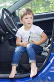 Boy with road map sits in car — Stock Photo