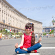 Stock Photo: Smiling girl sits in lotus position on main street of Kiev, Ukraine